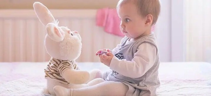 tavşan ile oynayan bebek