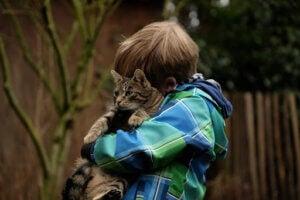 kediye sarılmış çocuk