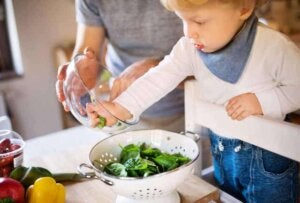 Küçük bir çocuk mutfakta annesinin yardımıyla yiyecek hazırlıyor.