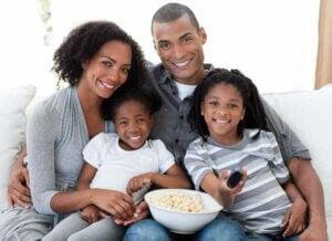 Anne baba ve iki kızı birlikte film izleyip mısır yiyorlar.