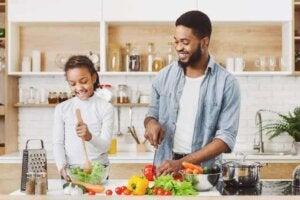 Mutfakta baba biber kesiyor kızı salatayı karıştırıyor.