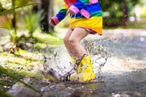 Su birikintisine atlayan çocuk