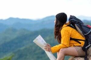 Bir kadın doğada bir taşa oturmuş elinde harita var.
