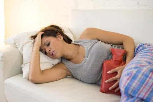 Regl döneminde karın ağrısı çeken kadın