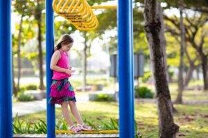 Parkta bir kız çocuğu yalnız başına düşünüyor yere bakıyor.