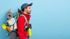 Sırtında çanta,mat ve boynunda matara ve fotoğraf makinası olan bir adam