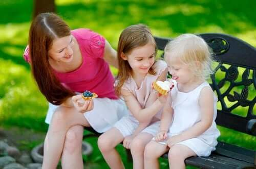 Çocukları ile bir parkta tatlı yiyen bir anne.