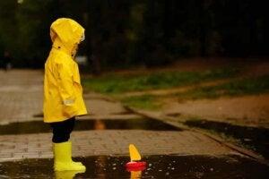 Yolda bir çocuk yalnız başına oyuncağına bakıyor.
